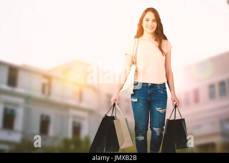 Beautiful brunette women holding bags against low angle view of city buildings on sunny day - Stock Photo