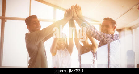 Portrait of business people raising hands seen through glass at creative office - Stock Photo