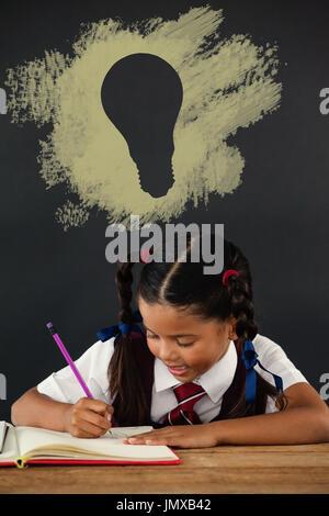 Digital composite image of light bulb on black spray paint against schoolgirl doing her homework against chalkboard - Stock Photo