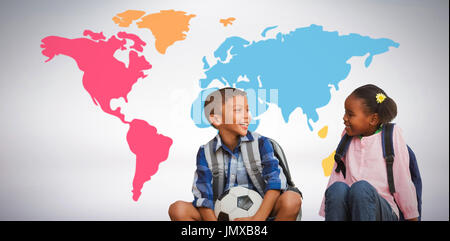 Boy with friend holding soccer ball against grey background - Stock Photo
