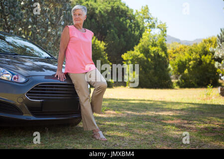 Thoughtful senior woman leaning on her new car - Stock Photo