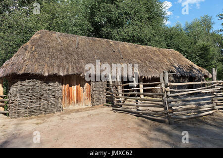 The old traditional woven Ukrainian rural barn with a thatched roof and a wooden fence around it in the courtyard - Stock Photo