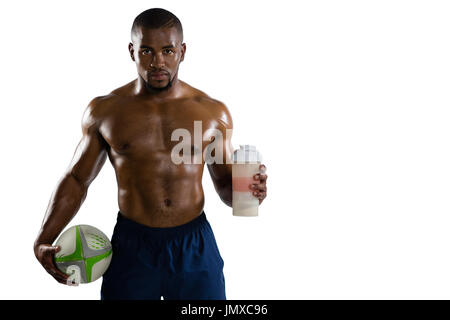 Portrait of shirtless sportsman with rugby ball holding drinking bottle while standing against white background - Stock Photo