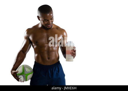 Shirtless sportsman with rugby ball holding drinking bottle while standing against white background - Stock Photo