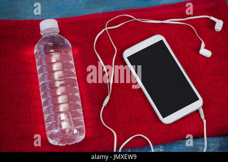 High angle view of water bottle and mobile phone with in-ear headphones on red napkin over table - Stock Photo