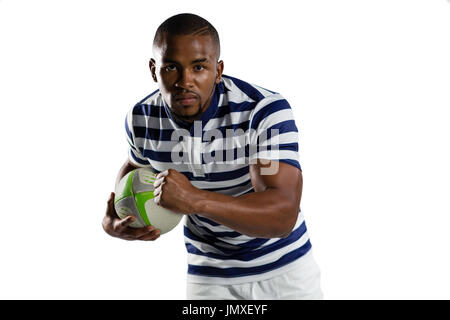 Portrait of young sportsman with ball running while playing rugby against white background - Stock Photo