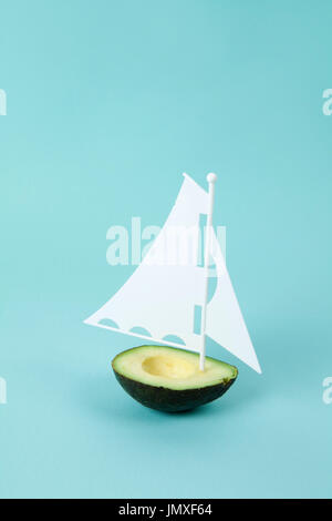 avocado half with white sail on a turquoise background. minimal and quirky color still life photography - Stock Photo