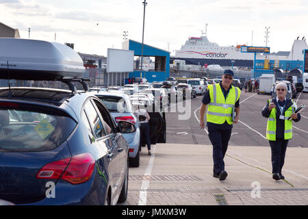 Portsmouth Harbour - staff working for the ferries with a queue of cars waiting to board a car ferry, Portsmouth - Stock Photo