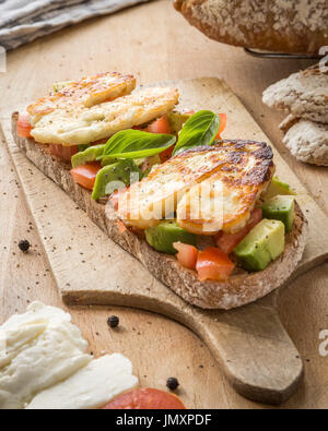 Toasted sourdough bread with Tomato, Avocado - Stock Photo