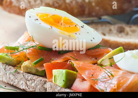 Toasted sourdough bread with Tomato, Avocado, Smoked Salmon and freshly boiled egg. - Stock Photo