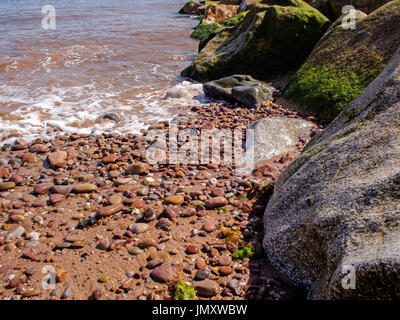 Water laps over smooth, rounded pebbles on a beach, showing gradation of deposits alongside a rock armour groyne. - Stock Photo