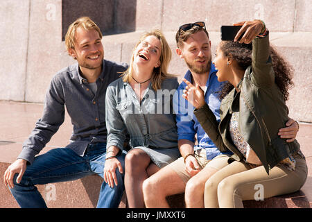 Group of smiling multiracial friends having fun while making selfie in the mobile phone Concept - Stock Photo
