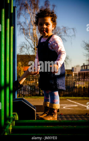 Portrait of a toddler who is playing in the playground. She is about to climb on the monkey bars - Stock Photo