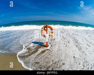 The waves reach the lifebelt in the deserted beach, even the sea is deserted - Stock Photo