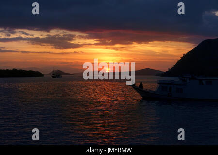 Silhouette of people sitting on ships watching the ocean sunset waiting for the giant bats to come out at night in Flores, Indonesia