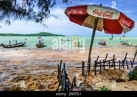 Phuket, Thailand - June 13, 2014: Traditional long-tail boats moored in bay as high tide floods over beach wall - Stock Photo