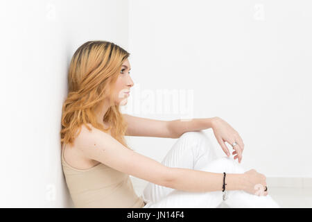 Young girl is sitting in an empty room. With sad and distant look on white wall of an empty room - Stock Photo