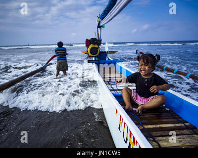 Airkuning, Bali, Indonesia. 29th July, 2017. A child sits in her family's outrigger fishing canoe while her father - Stock Photo