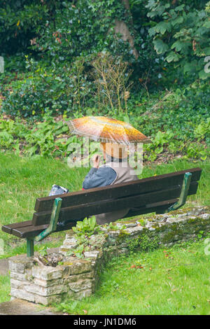 Bournemouth, Dorset, UK. 29th July, 2017. UK weather: rain doesn't stop this woman sitting in a park under her umbrella - Stock Photo
