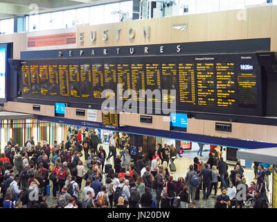 View of the departure board in the busy crowded concourse of London Euston Station - Stock Photo