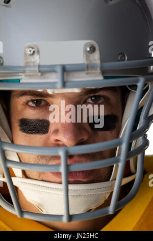 Close-up portrait of determined American football player wearing helmet