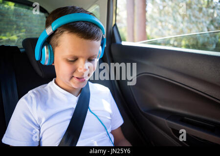 Smiling teenage boy with headphones sitting in the back seat of car - Stock Photo