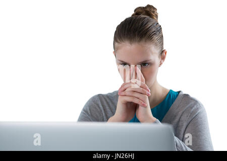Thoughtful teenage girl using laptop against white background - Stock Photo