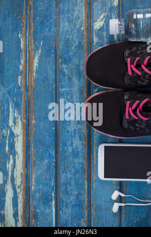Overhead view of sports shoes by mobile phone with in-ear headphones and water bottle on blue wooden table - Stock Photo