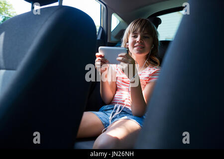 Happy teenage girl in headphones using mobile phone in the back seat of car - Stock Photo