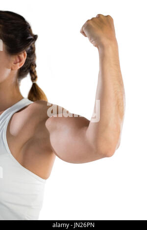Cropped image of female athlete flexing muscles against white background - Stock Photo