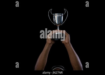 Cropped hand on sportsperson holding trophy against black background
