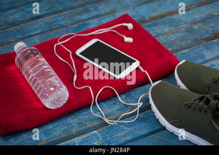High angle view of water bottle with mobile phone and in-ear headphones on napkin by sports shoes over blue wooden - Stock Photo
