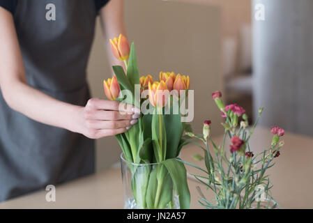 Mid section of woman arranging tulips in vase on table at cafe - Stock Photo