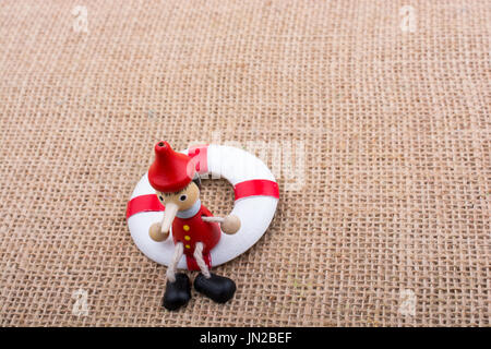 Pinocchio doll tied to a life preserver on canvas - Stock Photo