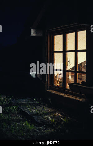 Wooden window details, part of an old wooden house during night. - Stock Photo