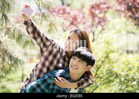 Young couple taking self portrait with mobile phone - Stock Photo
