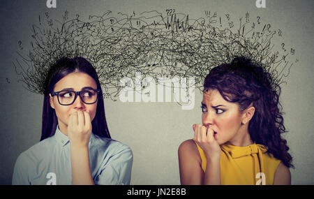 Side profile of two preoccupied anxious women looking at each other exchanging with many thoughts - Stock Photo