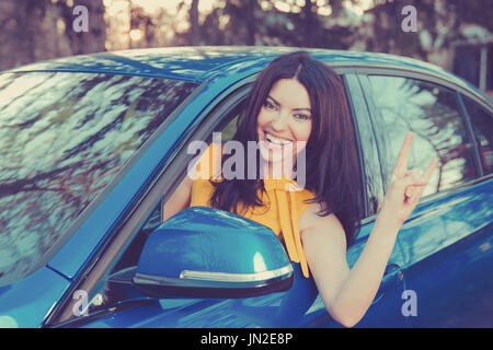 Traveling with fun. Happy young woman enjoying road park trip in her new car - Stock Photo