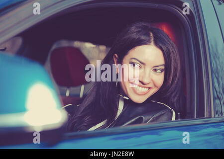 Traveling with fun. Happy young woman enjoying road trip in her new car - Stock Photo