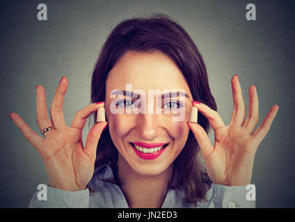Noise control. Woman holding ear plugs isolated on gray wall background - Stock Photo