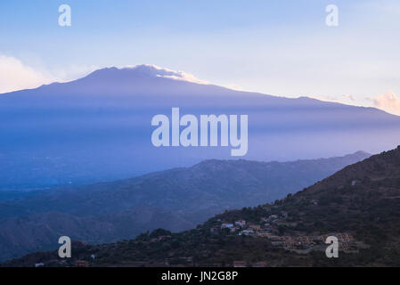 Etna Sicily, rays of the setting sun stream across Mount Etna and the hills surrounding Taormina in Sicily. - Stock Photo
