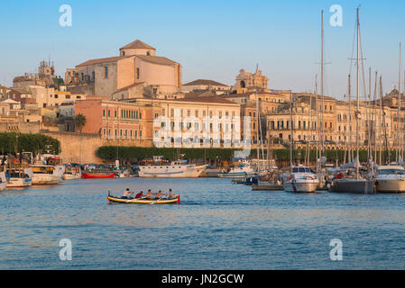 Syracuse Sicily cityscape, a rowing crew practise in the harbour (Porto Grande) of Ortygia (Ortigia), Syracuse, - Stock Photo