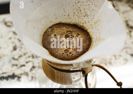 Fresh brewed black coffee bubbling in a white cup on a rustic wood table, taken from a top view. - Stock Photo