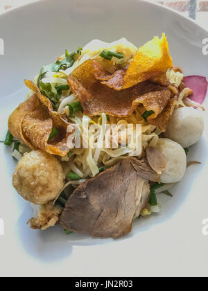 Asian Street Food. Closeup Egg noodle with red honey roasted pork (char siu, char siew) and fish meatballs and deep - Stock Photo