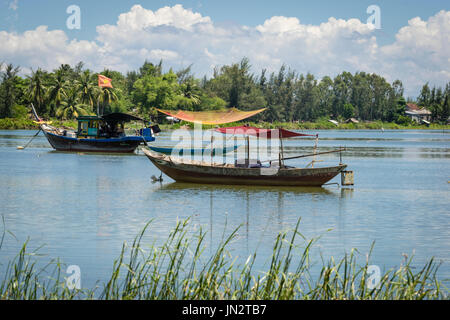 Old fashioned Vietnamese fishing boat and row boat moored on Thu Bon River outside Hoi An Vietnam - Stock Photo