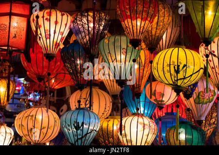 Many silk lanterns of various colors and designs hanging from a shop at night in Hoi An, Vietnam - Stock Photo