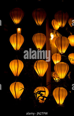 Silk lanterns glowing in the evening in Hoi An, Vietnam, known for its lantern designs - Stock Photo