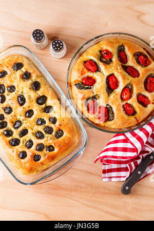 Two homemade Italian focaccia with olives and cherry tomatoes on a wooden table - Stock Photo