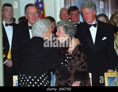 Former first lady Barbara Bush and former first lady Lady Bird Johnson speak to one another in the Grand Foyer of the White House at the 200th Anniversary of the White House Dinner in Washington, D.C. on November 9, 2000.  Looking on are former U.S. President George H.W. Bush and U.S. President Bill Clinton. Credit: Ron Sachs / CNP