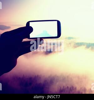 Smart phone mobile photography of sunny rocky mountains landscape, beautiful misty spring day - Stock Photo